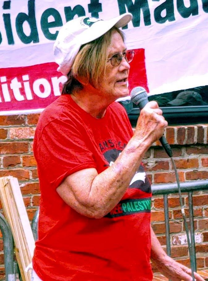 Photo of Ann Wright, an older white woman, speaking into a microphone.