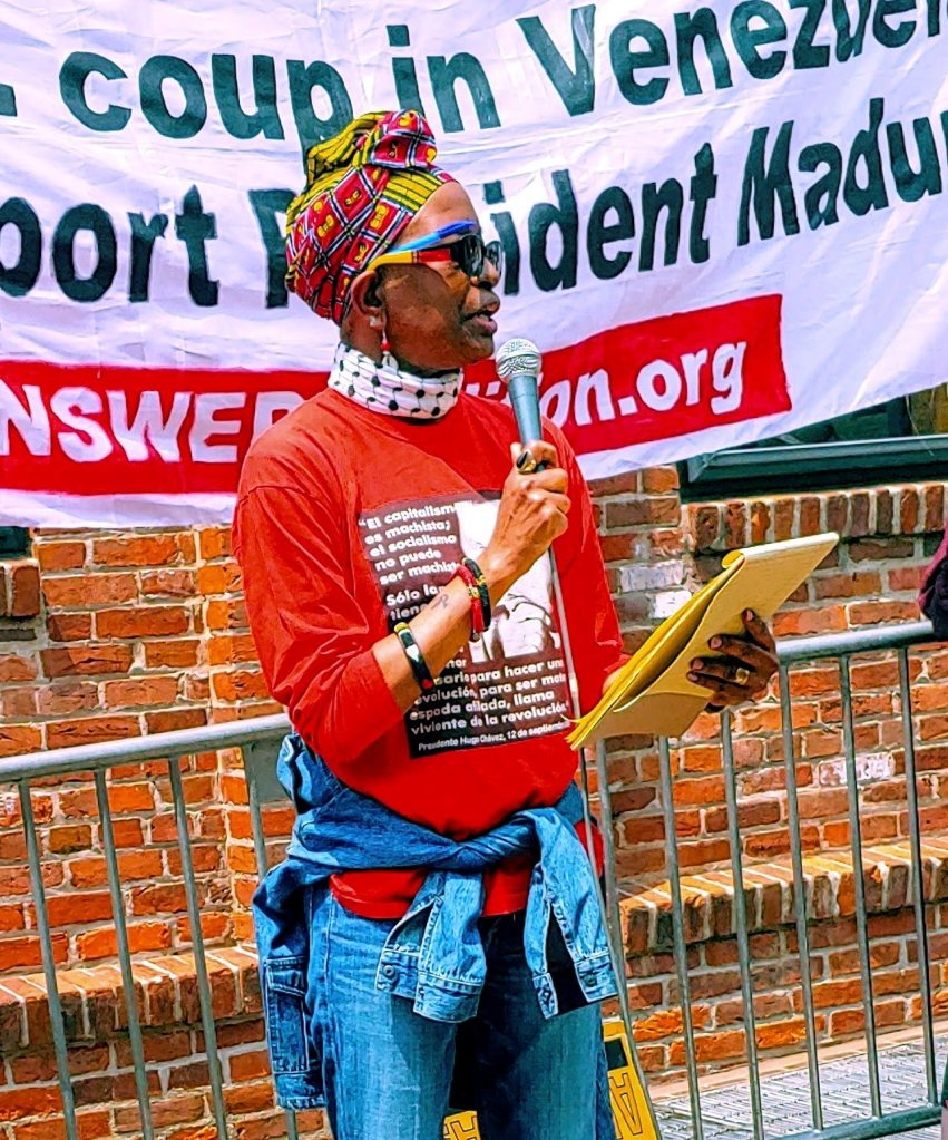 Photo of Asantewaa Nkrumah-Turi, a Black woman, speaking into a microphone in front of a banner.