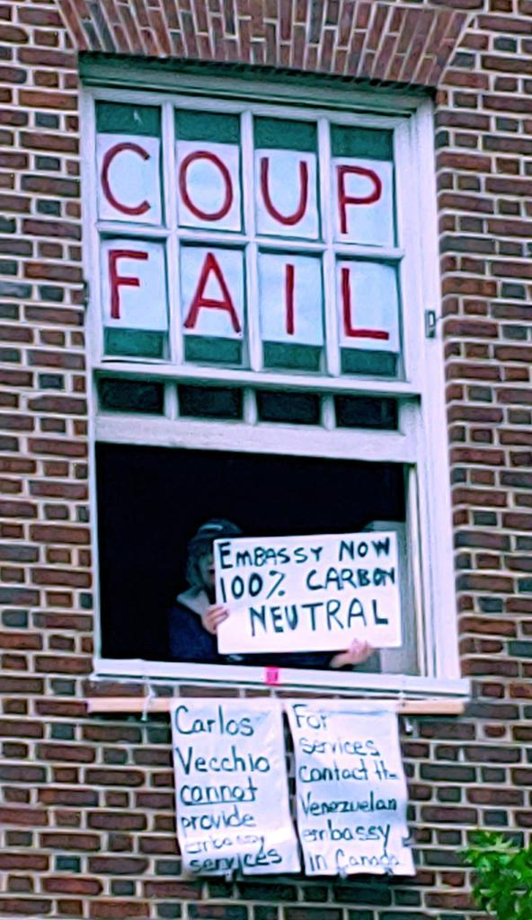 "Photo of an embassy protector in a darkened window, holding a sign that reads ""Embassy now 100% Carbon Neutral."" Around the figure are other signs that say: ""COUP FAIL,"" ""Carlos Veccio cannot provide embassy services,"" ""For services contact the Venezuelan embassy in Canada."""