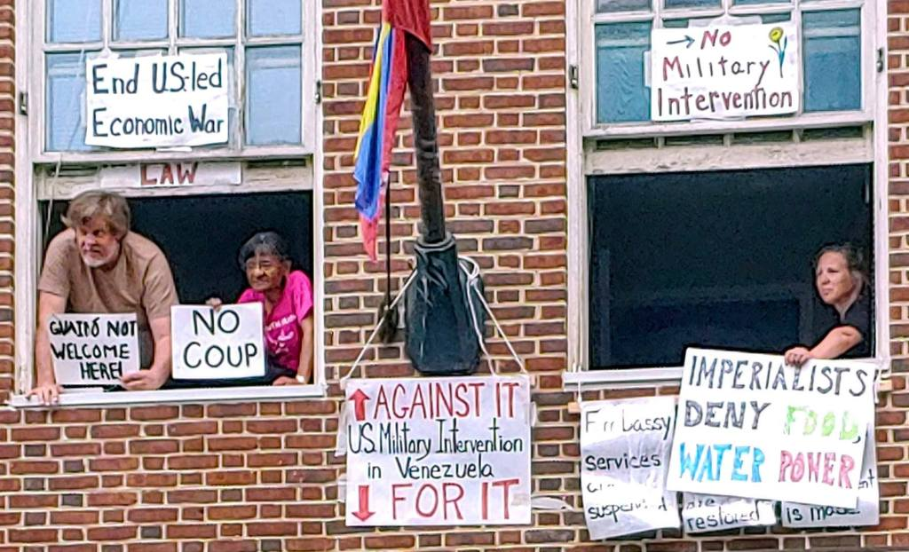 """A close-up photograph of three Embassy Protectors in their upper-floor windows. They hold signs which read: """"Guaido not welcome here,"""" """"No coup,"""" """"Imperialists deny food, water, power."""""""