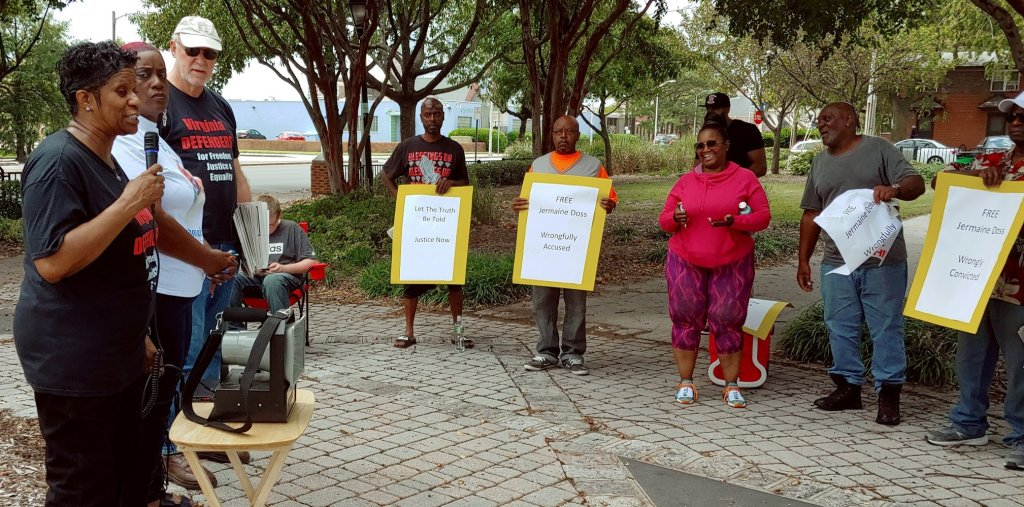 "Photo of a Black woman speaking to nine people attending an outdoor press conference. The group is majority-Black. Four hold signs: ""Let the Truth be Told, Justice Now""; ""Free Jermaine Doss, Wrongfully Accused""; ""Free Jermaine Doss, Wrongfully Convicted."""
