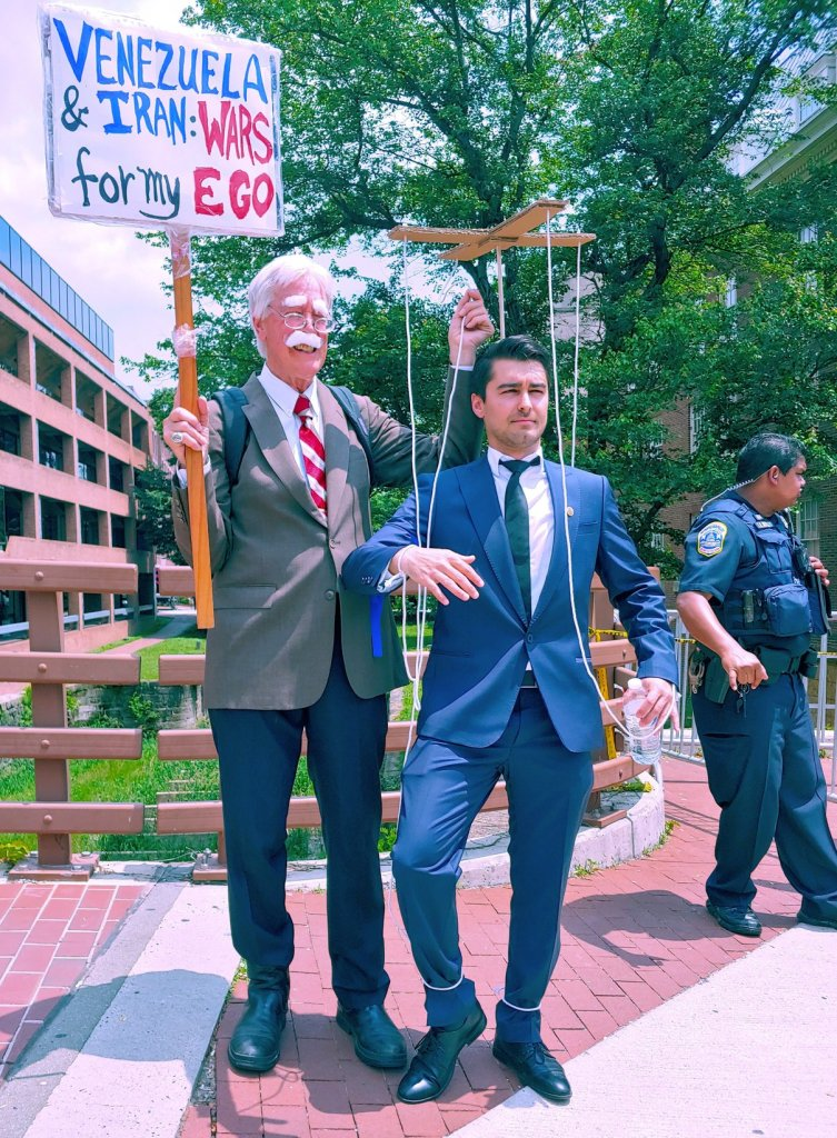 """Photograph of two men: one is dressed as a satirical depiction of U.S. National Security Advisor John Bolton and holds up a sign which reads, """"Venezuela and Iran: Wars for my Ego"""". In his other hand he holds an apparatus to control a marionette, which is connected to the other man with strings. The other man, who is posing as though he is a puppet, is dressed like Carlos Vecchio."""