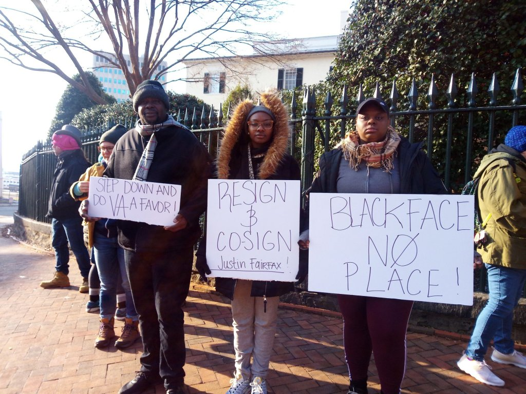 "Photo of six demonstrators holding signs in front of a fence outside of the governor's mansion. The signs read: ""Step down and do VA a favor!""; ""Resign and co-sign Justin Fairfax!""; ""Blackface No Place!"""