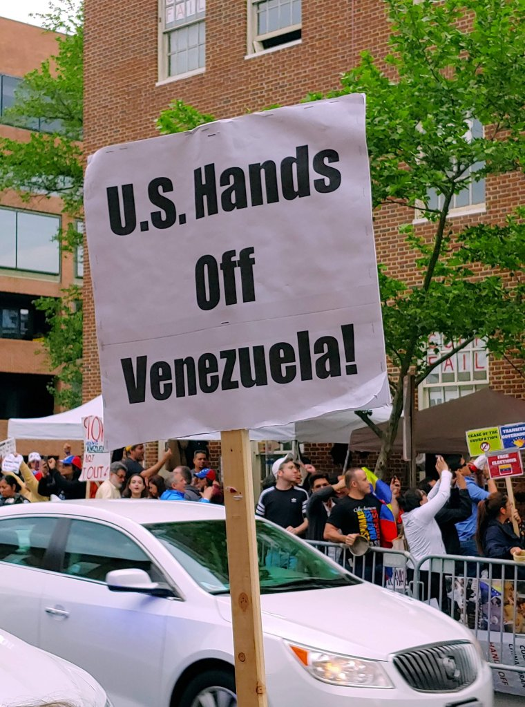 "Photograph of a sign which reads ""U.S. Hands Off Venezuela!"" in the foreground, with a view of a large crowd clustered around a brick building behind it."