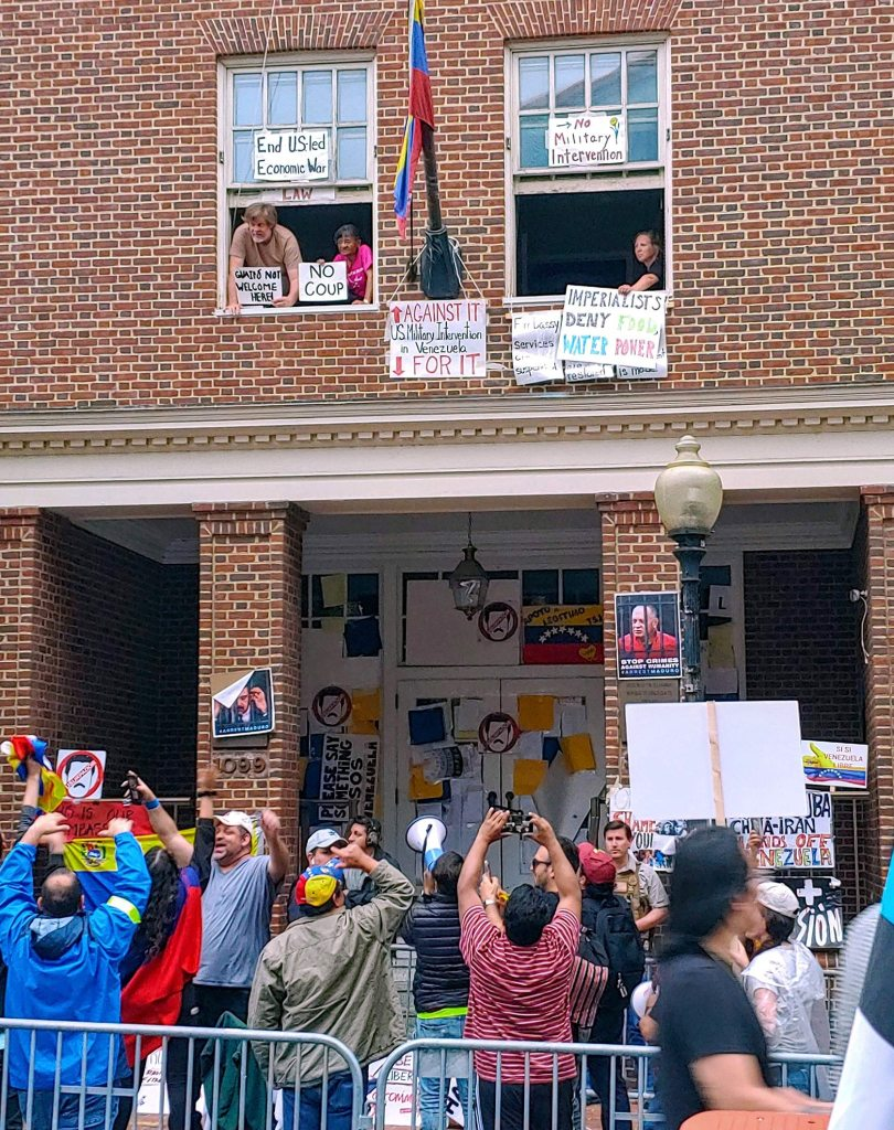 Photograph of the Venezuelan Embassy with a large crowd of coup supporters gathered around it as occupiers of the building look on from second-story windows festooned in anti-coup signs.