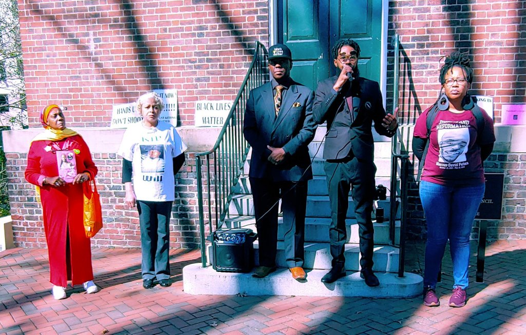 Photo of five people addressing a rally.
