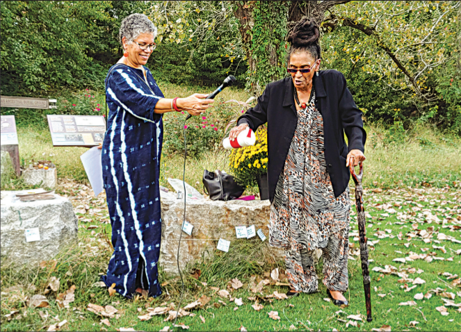Queen Nzinga, right, speaks and pours water from a container while Ana Edwards, left, holds a microphone for her. They stand outdoors among fallen leaves.