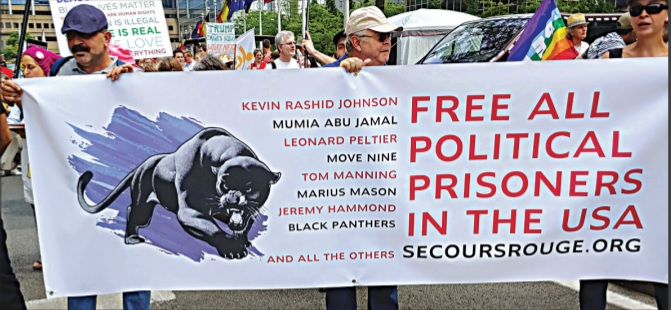 """Photograph of people holding a banner emblazoned with the phrase """"Free all political prisoners in the USA,"""" a short list of such prisoners, and an image of a black panther."""