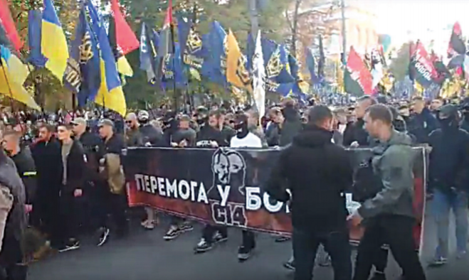 A very large crowd, primarily of young men, marching behind a black and red C14 banner.