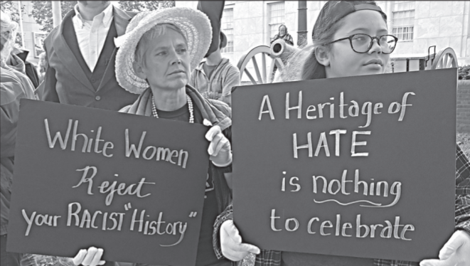 """Two women holding signs that read """"White women reject your racist 'history'"""" and """"A heritage of hate is nothing to celebrate""""."""