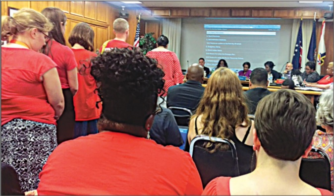 Photograph of a crowded school board meeting, with many audience members wearing red.