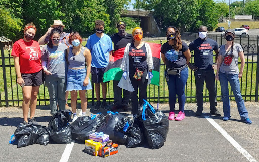 Photograph of a mixed-race group of ten people posing with several bags full of trash in front of Richmond's African Burial Ground.