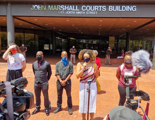 Photograph of Michaela Hatton and five others at a press conference in front of the John Marshall Court building in Richmond. Hatton is speaking.