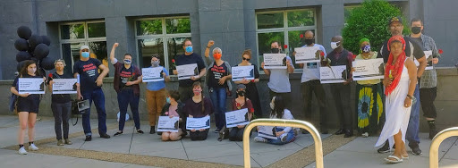 Photograph of 19 people with signs, roses, and black balloons gathered in front of a federal courthouse in Richmond.